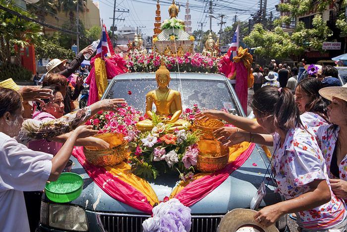 Hình ảnh người dân té nước vào hoa nhài vào tượng Phật
